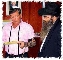 Nahariya's mayor Jacki Sabag dons tefillin with the Chabad emissary to Nahariya