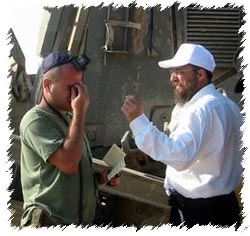 Rabbi Aaron Prus helps a soldier with tefillin.