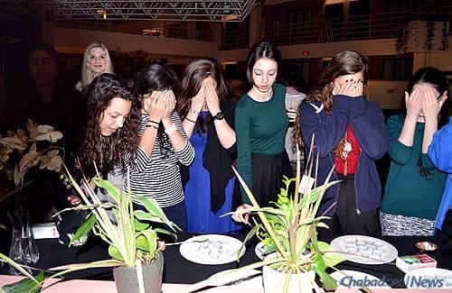 Récitant la bénédiction sur l'allumage des bougies du Chabbat.