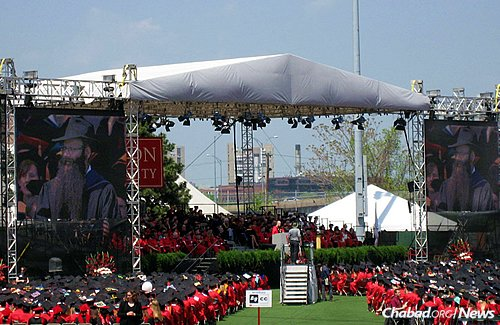 Dr. Binyomin Abrams, a senior lecturer of chemistry in the College of Arts & Sciences at Boston University, won the school's Metcalf Award for Excellence in Teaching. He is shown on jumbo screens on the right and left at commencement on Sunday, when he was presented with the honor.