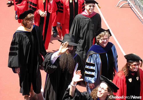 Giving a wave to the crowd on May 17 during Boston University's graduation ceremony, where he walked with other colleagues.