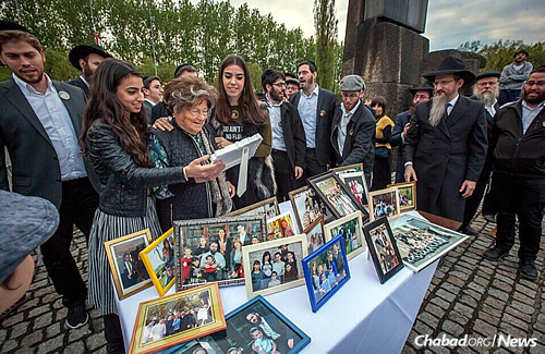 Outside the Auschwitz death camp in Poland, grandchildren of Holocaust survivor Breindel Fleishman present her with framed photographs of her descendant's families. (Photo: Eli Itkin)