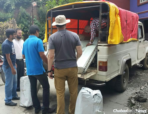 Rabbi Chezky Lifshitz, second from left, with workers and volunteers, supervises the loading of tents and supplies to be distributed throughout the devastated country. (Photo: Chabad of Nepal)