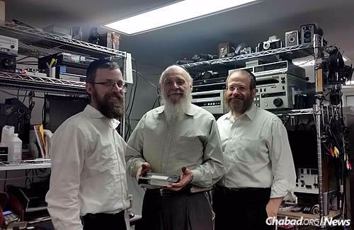 Director of JEM Rabbi Elkanah Shmotkin, left, with Baruch Bongart, holding a tape that was missing for years; next to him is his son Yisroel. After many hours of searching, the VHS tape was finally recovered. (JEM Photo)