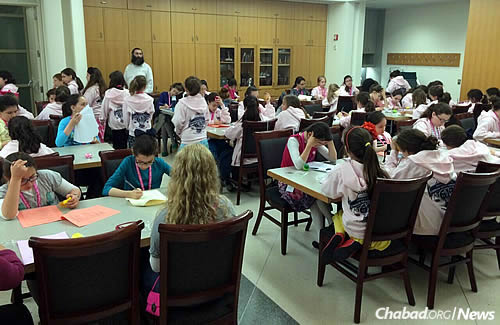 Getting down to business; 115 female finalists participated in the program, but only the two top scorers from each grade in each school took the actual final exam. Rabbi Shimmy Weinbaum, program director at Tzivos Hashem, is monitoring in the back.