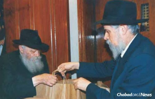 """Handing over a bag of gifts and momentos people had given to the Rebbe during Sunday """"dollars distribution."""""""