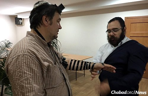 Although the elderly have mostly remained in the war-torn regions, some younger people have stayed, like this man wrapping tefillin with Rabbi Shalom Gopin. The city's rabbi and Chabad-Lubavitch emissary returned home last week for the first time since war caused him to leave out a year ago.