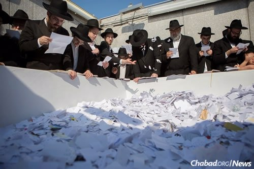 Visitors place letters at the resting place. (Photo: Adam Ben Cohen/Chabad.org)