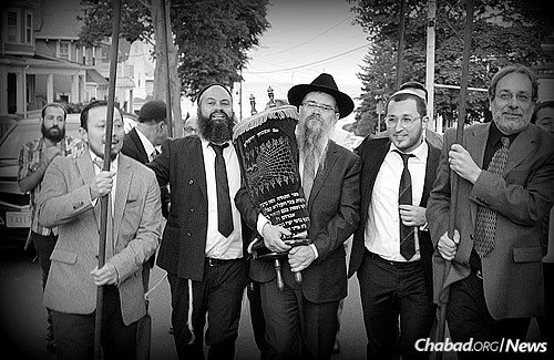 Walking the Torah in a procession from Ahabat Sholom in Lynn, Mass., to Chabad of the North Shore, where the rededication ceremony took place.