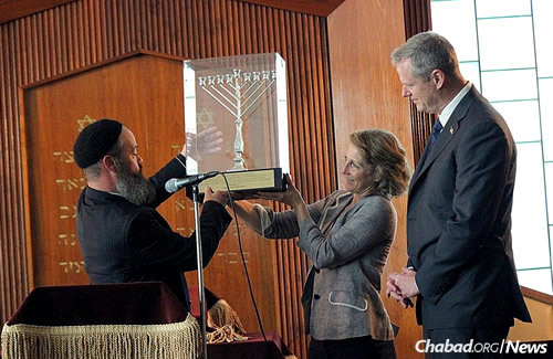 The rabbi presents the Bakers with the Lamplighter Award and a menorah at Chabad of the North Shore's 23rd anniversary gala.