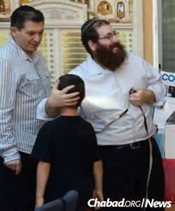 The rabbi with students and parents at the local Hebrew school that he directs. (Photo: Chabad of Mt. Olympus)