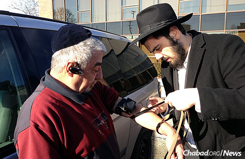 A mitzvah familiar to the yeshivah student: Helping a man don tefillin. (Photo: Lubavitch Mesivta of Chicago)