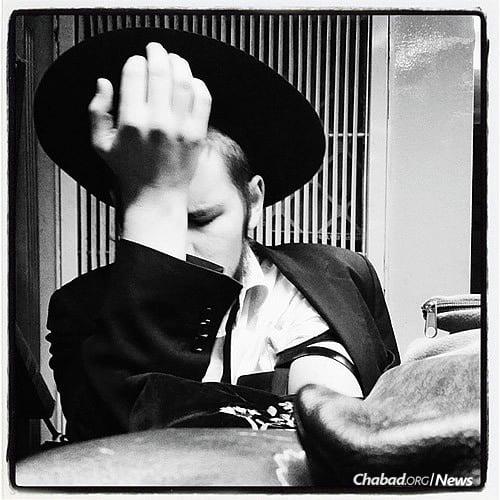 A yeshivah student engaged in prayer adjusts his tefillin. (Photo: Mordechai Lightstone)