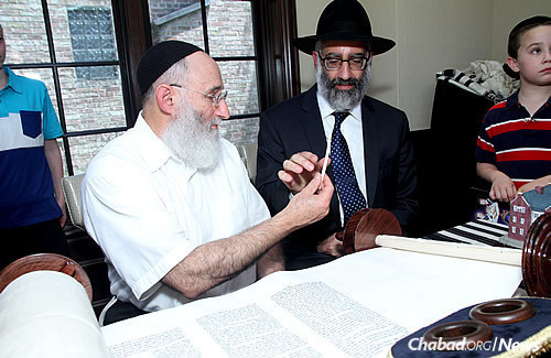 With the help of scribe Yochanan Nathan, left, in Chicago on Sunday, Gabriel Sassoon wrote the final letter in a new Torah scroll in memory of seven of his children who perished in a house fire three months ago on Brooklyn, N.Y. (Photo: Deja Views)