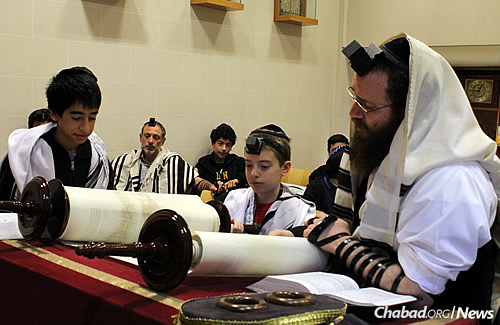 Shacharit morning prayers at Wolfsohn. Gurevitch, right, reads from the Torah as a student receives an aliyah.