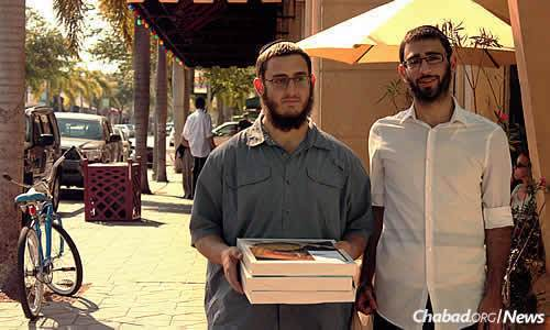Lew and Rosenthal hand out boxes of shmurah matzah for Passover on the streets of Lake Worth.