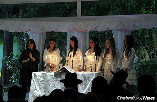 A bat mitzvah ceremony at the school, with the young women lighting symbolic Shabbat candles and receiving their own set of candle holders. At left is Wolfsohn's co-director, Lea Gurevitch.