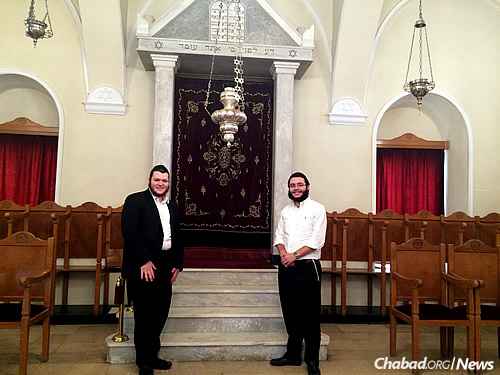 Between visits with Jewish shopkeepers and others, rabbinic students Mendel Wolowik, left, and Mendel Tubul took time for prayer (and a photo) in the synagogue that serves the ancient Jewish community of Larissa.