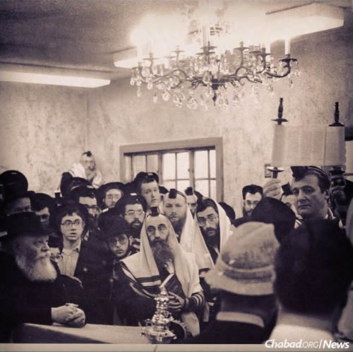 "The Rebbe, left, and worshippers at 770 Eastern Parkway look on as Jerry Weintraub, right, is given the honor of ""hagbah,"" raising the Torah scroll at the completion of the midweek reading."