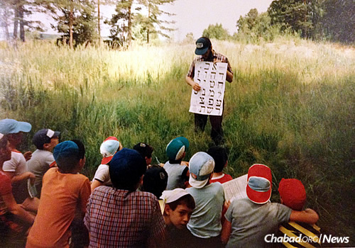 """Despite wide language differences, the first batches of American yeshivah-students-turned-counselors at Camp Gan Israel managed to find a way to communicate with their young Russian-Jewish charges. Here, a counselor introduces his campers to the """"alef-bet"""" in the summer of 1990."""