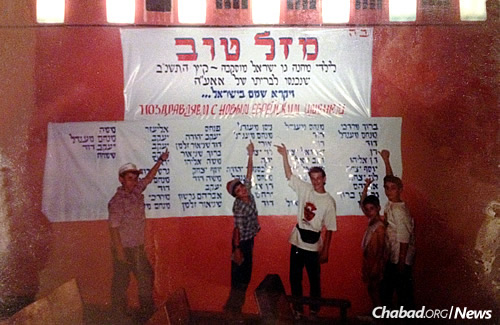 """Five boys point to their new Jewish names on a """"Mazal Tov"""" sign celebrating circumcisions in Moscow in 1992. Altogether, there are 54 names on the list—boys who reclaimed the heritage denied to them for generations."""