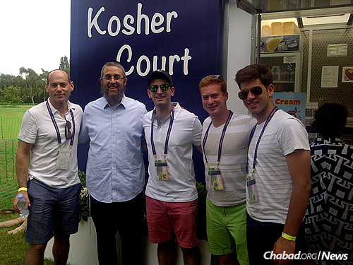 Cohen poses with a group of Jewish tennis fans, happy for the chance to fill up on hot dogs, burgers, baked potatoes and Wimbledon's signature snack—strawberries and (nondairy) cream.