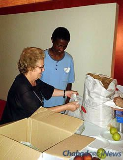 A woman in Milan packs fruit and other items for incoming refugees.