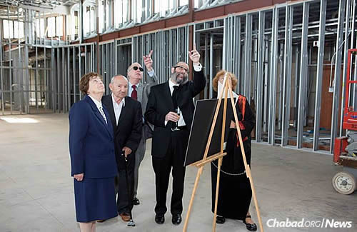 The rabbi gave tours of the building to visitors while the structure was going up.