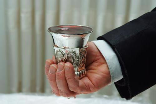 Holding the ceremonial cup of wine for Kiddush or Havdalah.