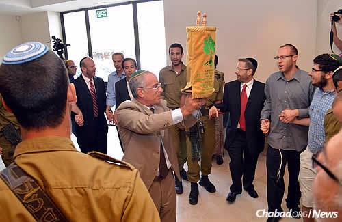 Stuart Steinberg displays the new Torah to the crowd. Its smaller size makes it easier for IDF troops to carry it with them. (Photo: Lone Soldier Center)