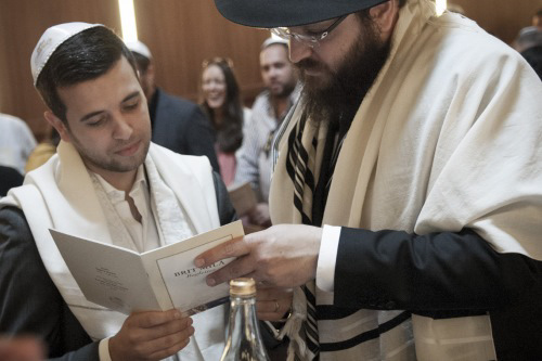 A mohel assisting a father to read the text. Photo: Clifford Lester