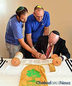 Writing the last letters in the Torah are director of the Lone Soldier Center Josh Flaster, left, and adviser Jared White. (Photo: Lone Soldier Center)