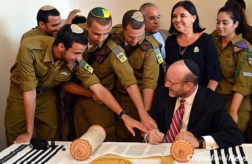Soldiers reach to assist sofer (scribe) Ronnie Sieger in writing the last letters of the Torah; next to them are Max Steinberg's parents, Stuart and Evie Steinberg. (Photo: Lone Soldier Center)
