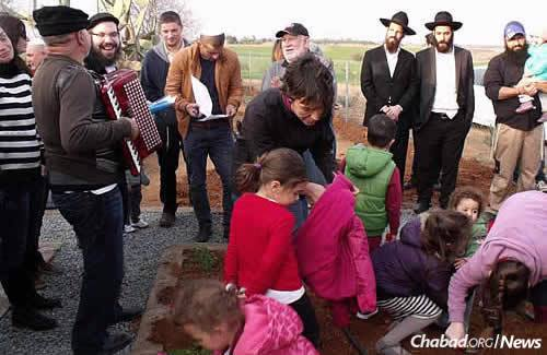 Adults and kids add trees to the landscape at a communal event.