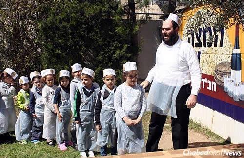 "Rabbi Raskin instructs children at a ""Model Matzah Bakery"" workshop prior to Passover."
