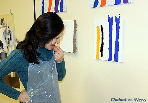Aislinn Wendrow, 22, examines some of her paintings at Soul Center Mini, the precursor to a new Friendship Circle of Michigan program where young adults with special needs can share their creative skills with the community.