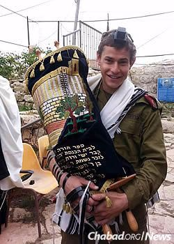 Holding the Torah in this bar mitzvah year.