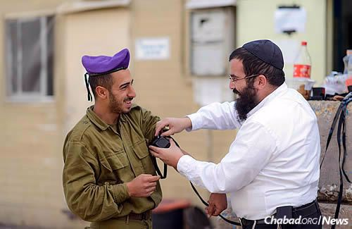 Rabbi Cohen helps a soldier put on tefillin.