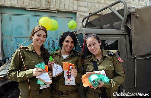 Soldiers hold snacks and letters from supporters in Israel and abroad, especially from children.