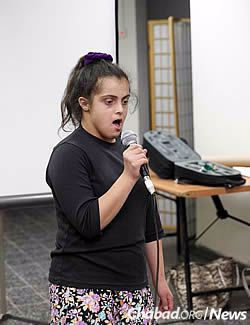 Noga Berlin, a child with special needs, shares her story at an event honoring teen volunteers.