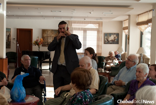 Rabbi Mendel Hendel, co-director of Chabad Lubavitch of Athens, blows shofar for seniors in Greece during the Hebrew month of Elul in preparation for Rosh Hashanah.