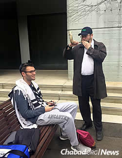 The rabbi blows shofar for James Ashton, who is donning tefillin at the start of the new year.
