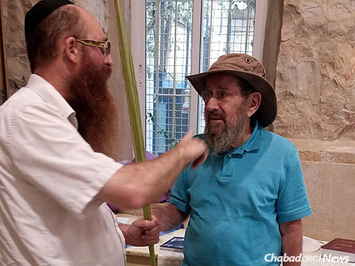 Rabbi Yosef Yitzchok Slonim, left, director of Beit Chabad of the Center of the City of Jerusalem, serves the ever-expanding needs of neighborhood residents, in addition to the throngs of daily and nightly visitors to the area. (Photo: Sarah Leah Lawent)