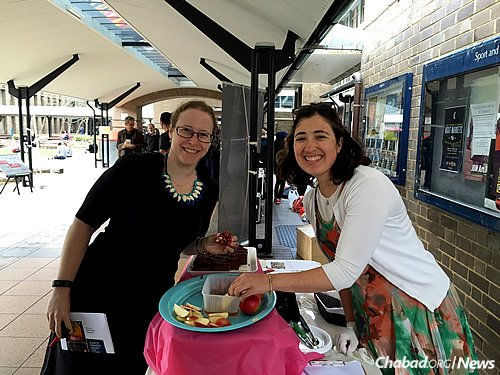 "Hadassah (""Dassi"") Leggett, right, who coordinates programming for university students as part of Young Adult Chabad in Bondi, Australia, offers apples, honey and honey cake for Rosh Hashanah."
