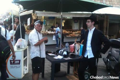 Yeshivah students wrapped tefillin with shoppers at the Machane Yehuda outdoor market in Jerusalem.