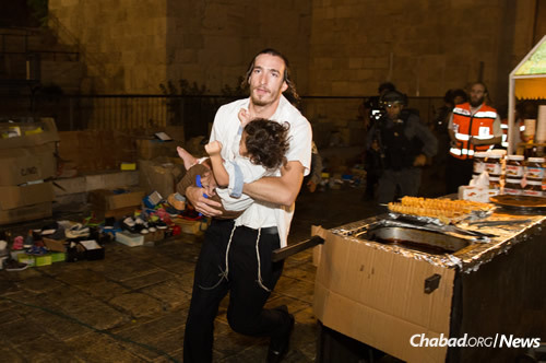 A man carries a baby injured in a knifing attack in the Old City of Jerusalem. A Jewish family and a second man were stabbed while walking near the Lion's Gate. (Photo: Yonatan Sindel/Flash90)