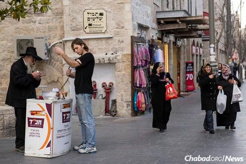 Helping passersby don tefillin on Jaffa Street in Jerusalem. (Photo: Flash/90)