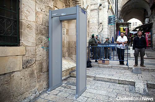 An Israeli guard in the Old City of Jerusalem stands near a metal detector placed there following a week of stabbings and terror attacks. (Photo: Yonatan Sindel/Flash90)