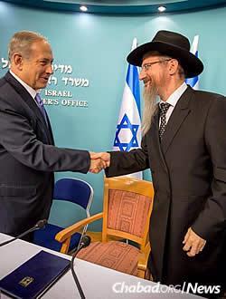 Israeli Prime Minister Bejamin Netanyahu greets Chief Rabbi of Russia Berel Lazar at a group meeting on Sunday night. (Photo: Ezekiel Itkin)