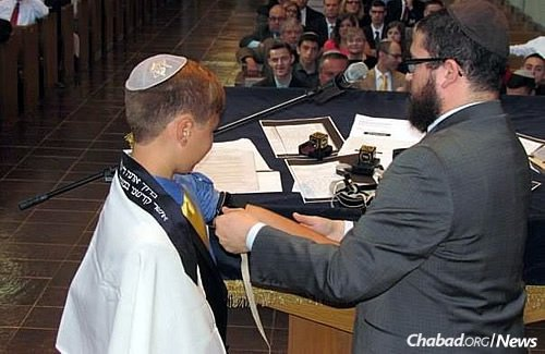 The rabbi helps Liam put on tefillin.
